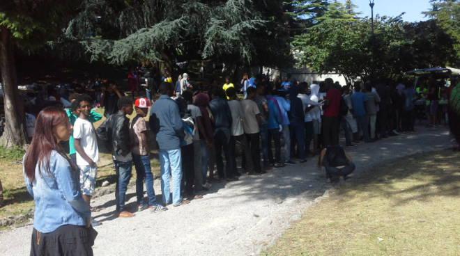 migranti in coda como per pasti