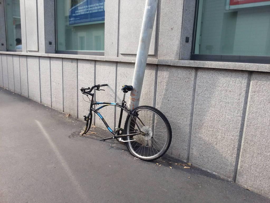 Como, via Rubini: il palo piegato e la bici senza una ruota