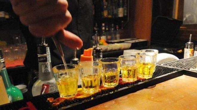 giovane beve da bottiglia e drink sul tavolo locale