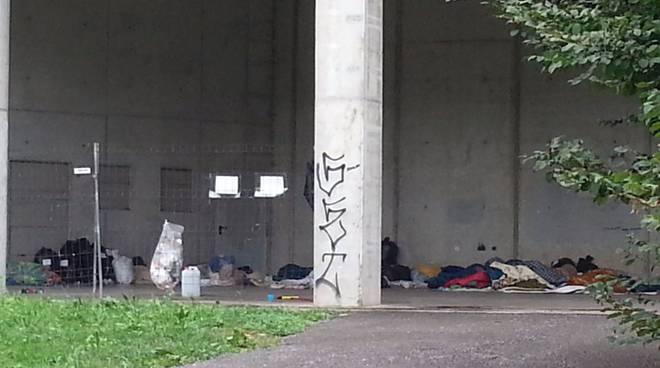 I profughi sotto l'autosilo della Valmulini: coperte e rifiuti