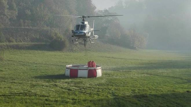 elicottero prende acqua per domare incendio bosco