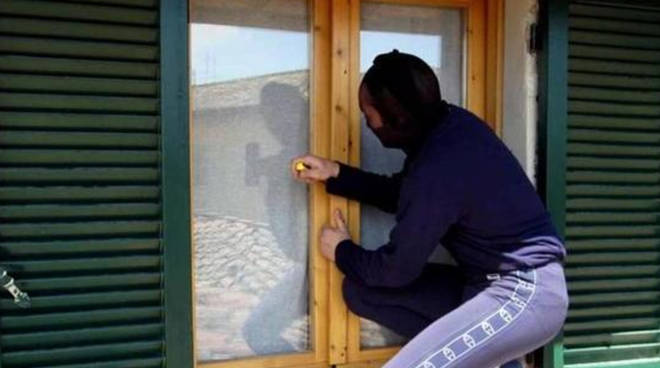 ladro che tenta di entrare in casa dalla finestra generico