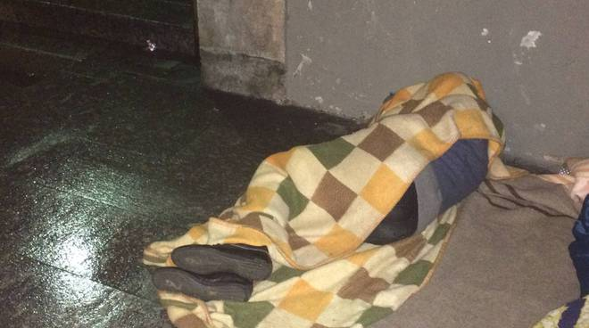 senza tetto di como dorme sul pavimento bagnato san francesco como