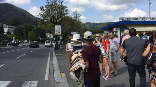 venditori abusivi di cappelli sul lungolago di como tanti anche oggi