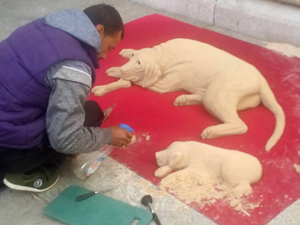 ragazzo che realizza i cani in sabbia esterno del duomo di como