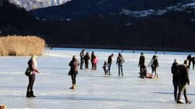 lago del piano carlazzo ghiacciato gente che ci pattina sopra