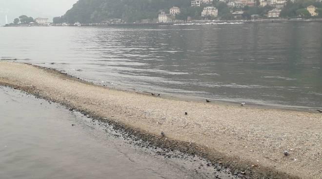livello del lago di como in calo, spiaggia sempre evidente dietro al tempio voltiano di como