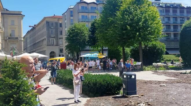 detriti e turisti a fare foto in piazza cavour dopo esondazione del lago stamattina