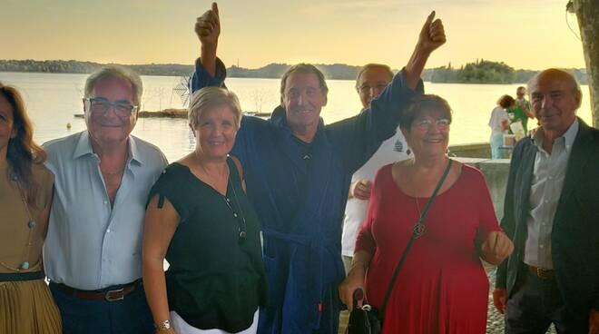 Leo Callone taglia il traguardo e poi festeggiato a pusiano dopo periplo del lago