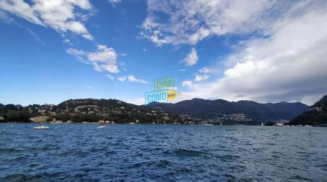 lago increspato per vento raffiche forti crescita livello e cielo con sereno e nuvole